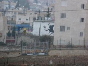 Banksy's seminal image of a molotov cocktail launching protester, altered to have him throwing a bouquet of flowers instead, in the West Bank