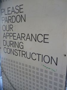 """Poster reads, """"Please pardon our appearance during construction"""". Added is, """"I forgive you!"""" in green pen."""