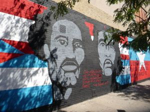 Stylised mural with images of Pedro Albizu Campos and Ernesto 'Che' Guevara blending into Puerto Rican and Cuban flags respectively, on a wall in Spanish Harlem